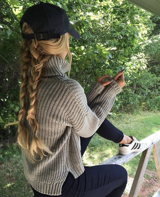 a duo of braids on the back and some hair down plus a black baseball cap for a casual look