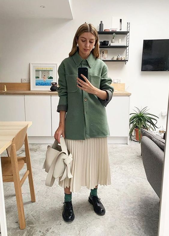 a green shirt jacket, a neutral pleated midi, green socks and black shoes plus a white bag