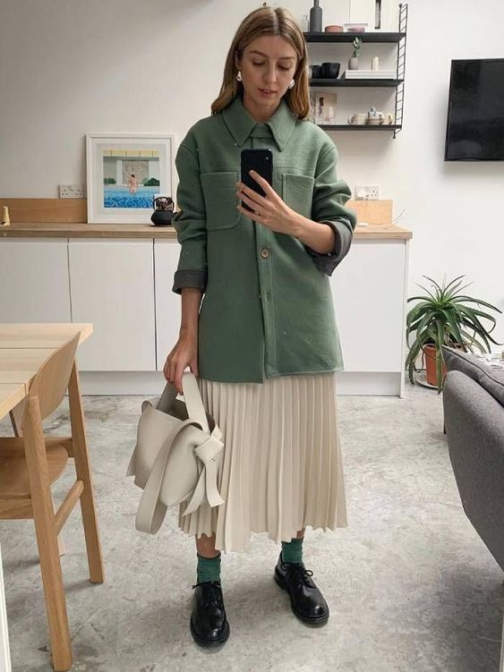 a green shirt-style jacket, a creamy pleated midi, black Derby shoes, green socks and a creamy bag