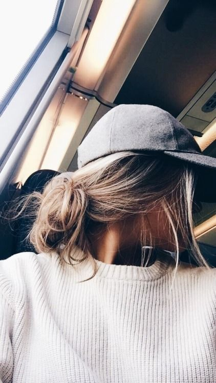 a grey baseball cap and a messy low bun plus some hair down for a simple last-minute look