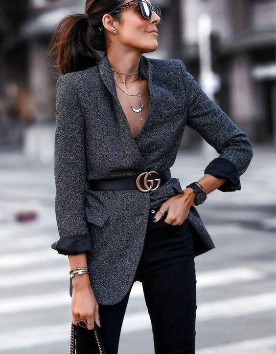 a grey blazer with a black belt, black jeans, a bracelet and layered necklaces to create a chic look