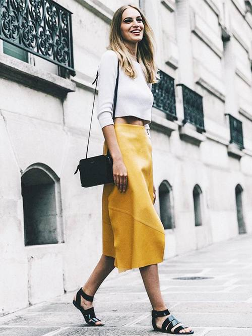 a grey cropped jumper, a high waisted yellow midi skirt, black strappy sandals and a black bag