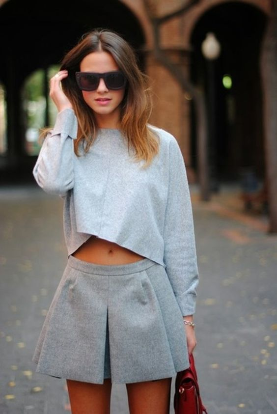 a grey look with a cropped sweatshirt and a pleated mini skirt plus a red bag is a stylish idea for spring