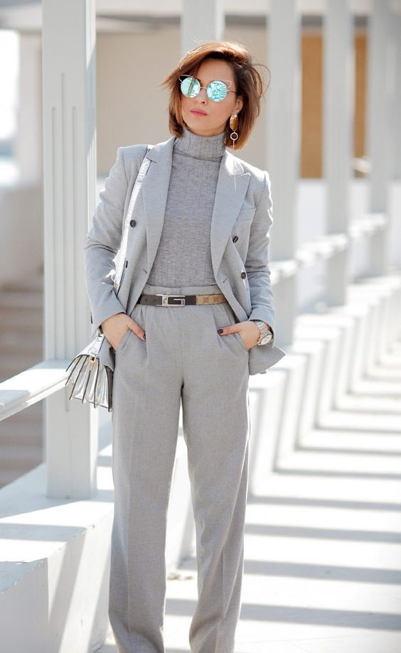 a grey pantsuit, a grey turtleneck, two tone brogues, a silver bag and a silver belt for work