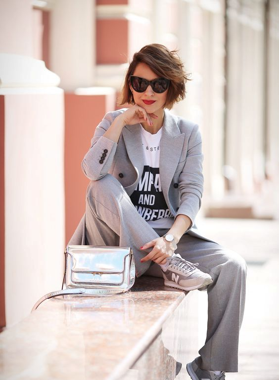 a grey pantsuit, a printed t-shirt, grey traiers and a silver bag for a comfortable work look