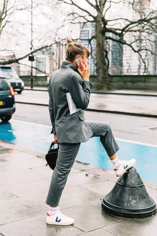 a grey pantsuit, white sneakers and socks, a black bag for a stylish work look