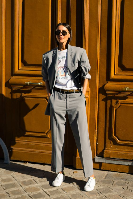 a grey pantsuit with an oversized blazer, a printed tee, white sneakers and a black clutch
