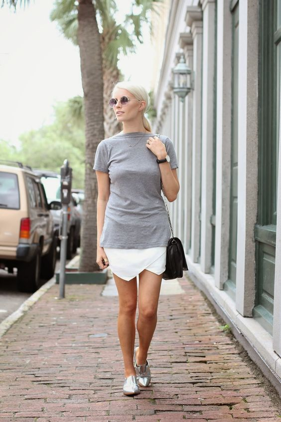 a grey tee, a white asymmetrical skirt, silver Oxford shoes and a black bag
