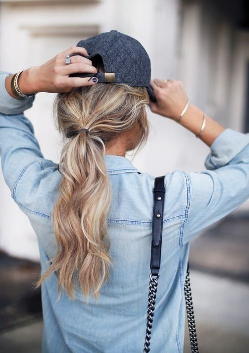 a low ponytail is a perfect match for a baseball cap, and it's very trendy this year