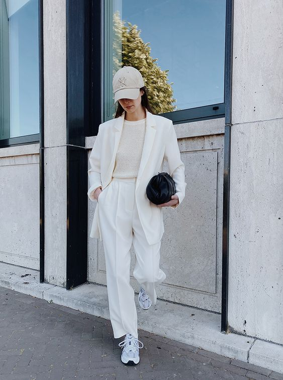 a minimalist work outfit with a white pantsuit, a neutral jumper spruced up with a tan baseball hat and white trainers