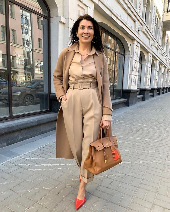 a monochromatic look with a tan shirt and trousers, red shoes, a camel coat and a camel bag