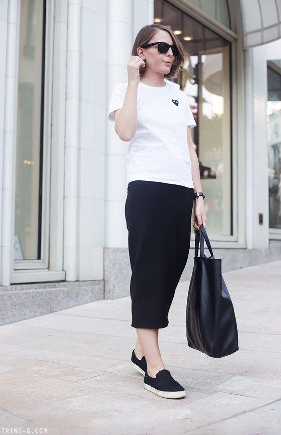 a monochromatic outfit with a white printed tee, black pencil midi, black slipons and a black tote