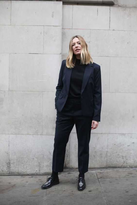 a navy pantsuit, a black turtleneck, black Derby shoes for a formal and very elegant work look