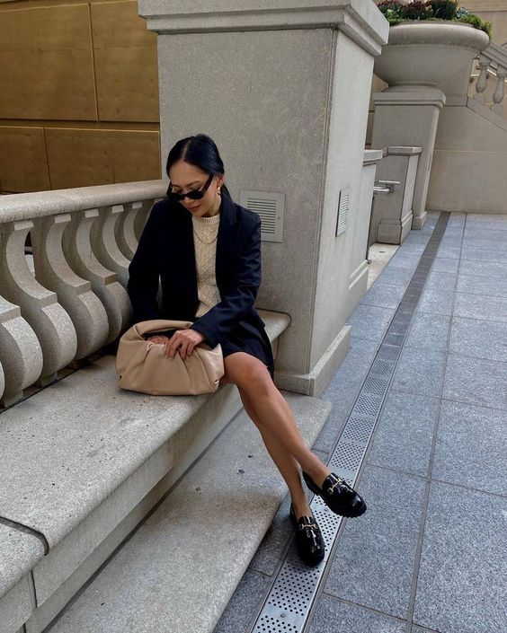 a navy skirt suit, a neutral jumper, black chunky loafers and a tan bag for work