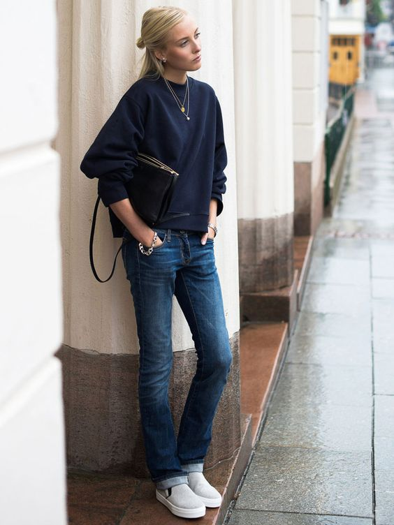 a navy sweatshirt, straight jeans, white slipons and a black bag plus layered necklaces