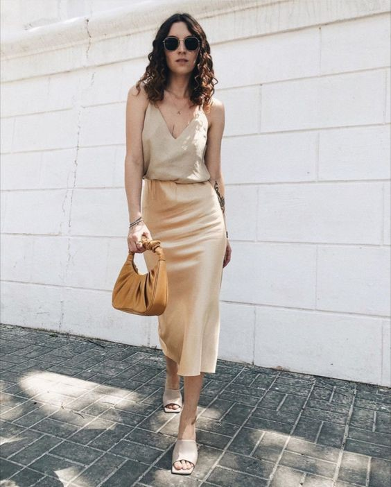 a neutral and very sexy look with a deep V-neckline slip top, a tan slip dress, neutral mules and a brown baguette bag