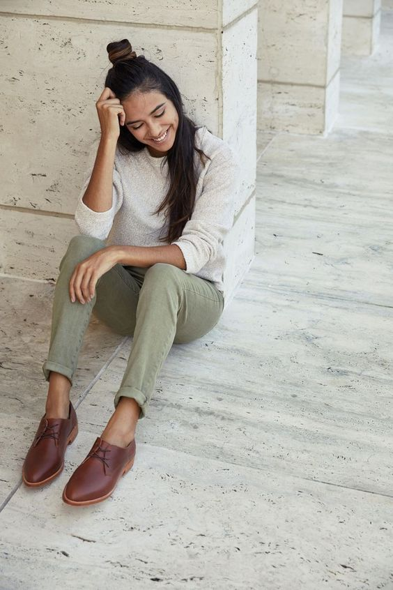 a neutral jumper, green jeans, brown Oxford shoes for a casual and comfortable work look