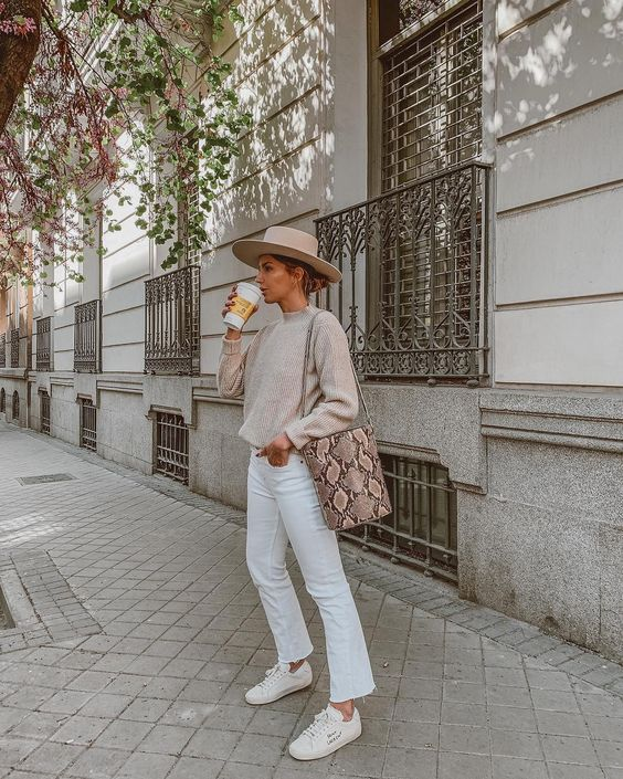a neutral jumper, white jeans, white sneakers, a tan hat and a snakeskin bucket bag