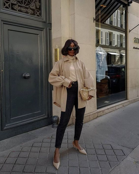 a neutral turtleneck, black skinnies, neutral shoes and an oversized shirt jacket plus a tan clutch