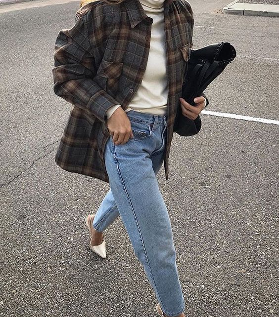 a neutral turtleneck, blue baggy jeans, silver shoes, a dark plaid shirt jacket and a black clutch