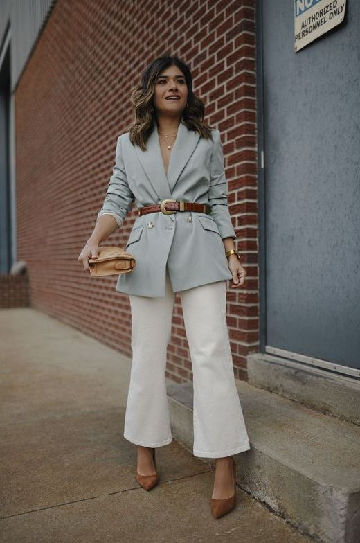 a pastel blue blazer with a brown belt, white flare jeans, brown shoes, a tan clutch for spring