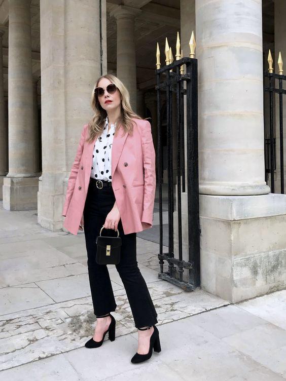 a polka dot blouse black flare jeans, black block heels, a pink blazer and a black bag