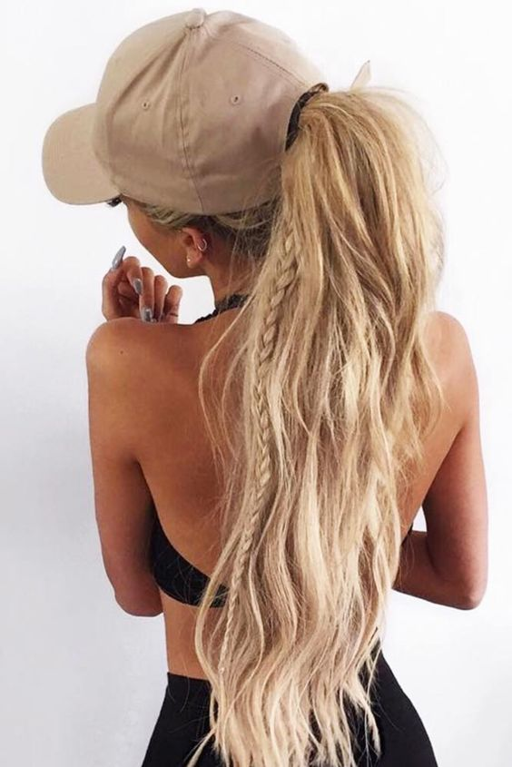 a ponytail with a little braid and textural hair plus a baseball cap for a chic and sexy look