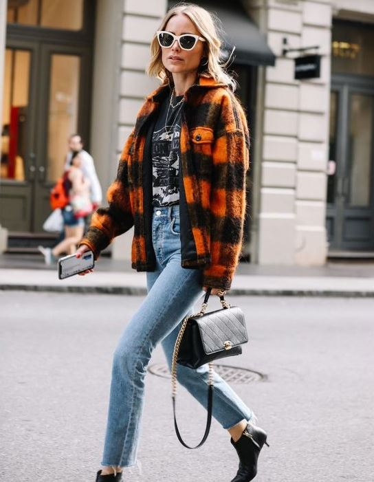 a printed black tee, blue jeans, black kitten heel boots, a bold plaid shirt jacket and a black bag