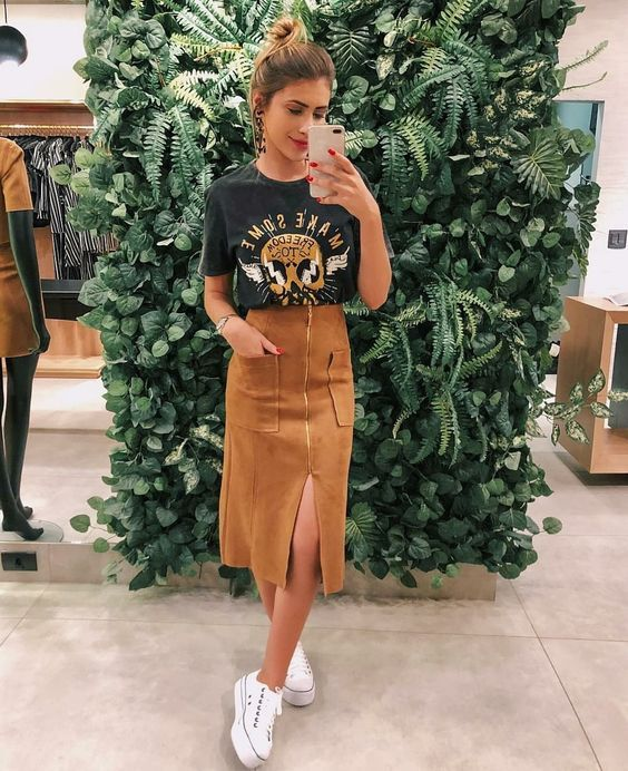 a printed t-shirt, a mustard suede midi skirt with pockets and white sneakers plus statement earrings
