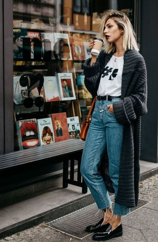 a printed t shirt, blue cropped jeans, black chunky loafers, a grey oversized cardigan and an amber bag