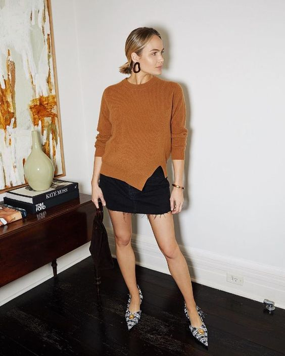 a rust colored jumper with a slit. a black denim mini skirt with fringe, printed whimsy shoes