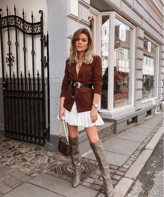 a sexy look with a brown blazer and a black belt, a white A-line mini skirt, grey boots, a brown bag
