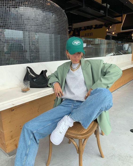 a spring look with a grey t-shirt, a green oversized blazer, blue jeans, white sneakers and an emerald baseball hat