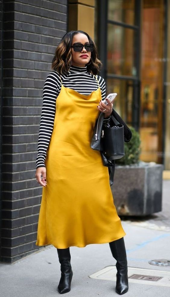 a striped turtleneck, a gold slip midi dress, black boots, a black leather jacket and a black bag