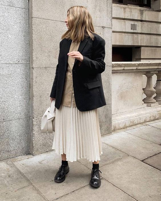 a tan oversized shirt, a creamy pleated midi skirt, a black blazer, black Derby shoes and a creamy bag