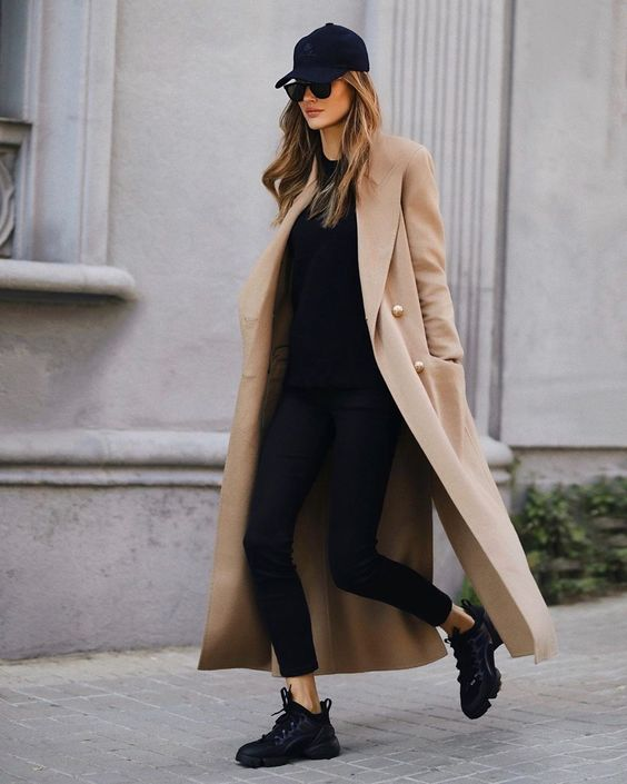 a total black look with a sweatshirt, leggings, trainers and a baseball hat plus a tan trench