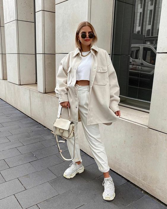 a white crop top, neutral trousers, neutral trainers, a neutral shirt jacket and a neutral bag