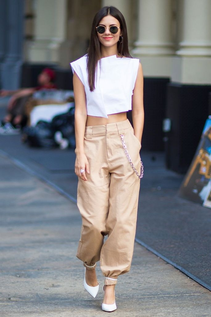 a white crop top, tan cargo pants with a chain and white shoes for a trendy and bold look