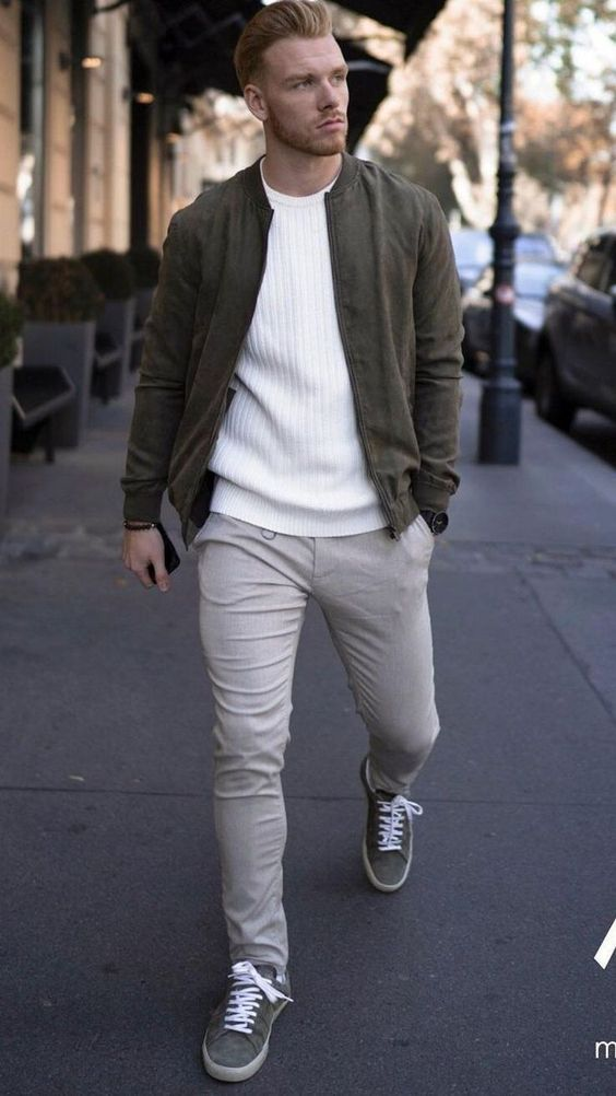 a white jumper, a green bomber jacket, grey pants, grey sneakers for a casual winter or spring date