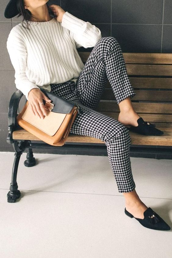 a white jumper, black and white plaid trousers, black mules and a color block oversized clutch