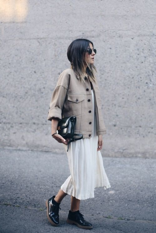 a white pleated midi dress, a tan oversized denim jacket with black buttons, black Derby shoes and a black bag
