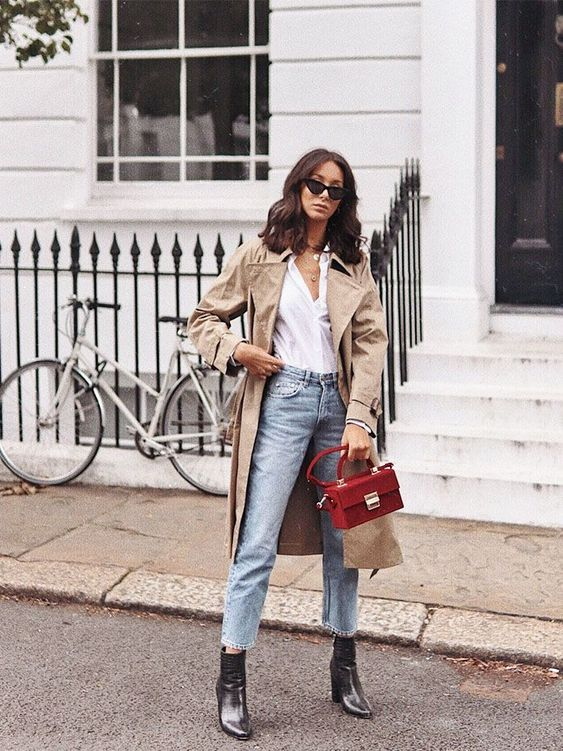 a white shirt, light blue jeans, black boots, a tan trench and a small red bag for spring