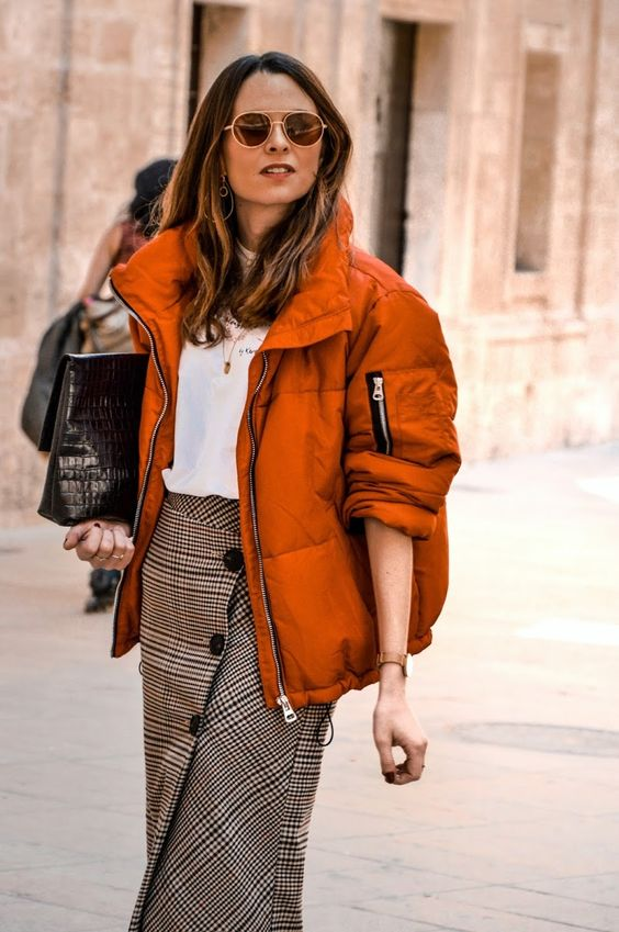 a white t-shirt, a plaid button up midi skirt, a burnt orange puffer jacket and a black oversized clutch