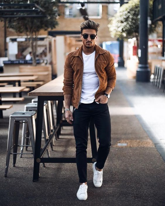 a white t-shirt, black jeans, a rust jacket and white sneakers for a comfy look with a touch of color