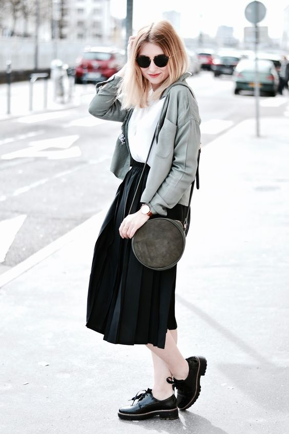a white t-shirt, black pleated midi skirt, a grey jacket, a graphite grey round bag and black shoes