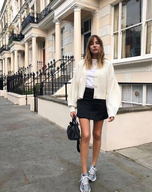 a white tee, a creamy cardigan with puff sleeves, grey trainers, a black mini skirt and a black bag