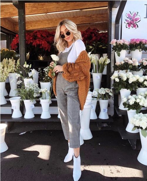 a white tee, a grey plaid overall, white ankle booties and a rust-colored oversized cardigan