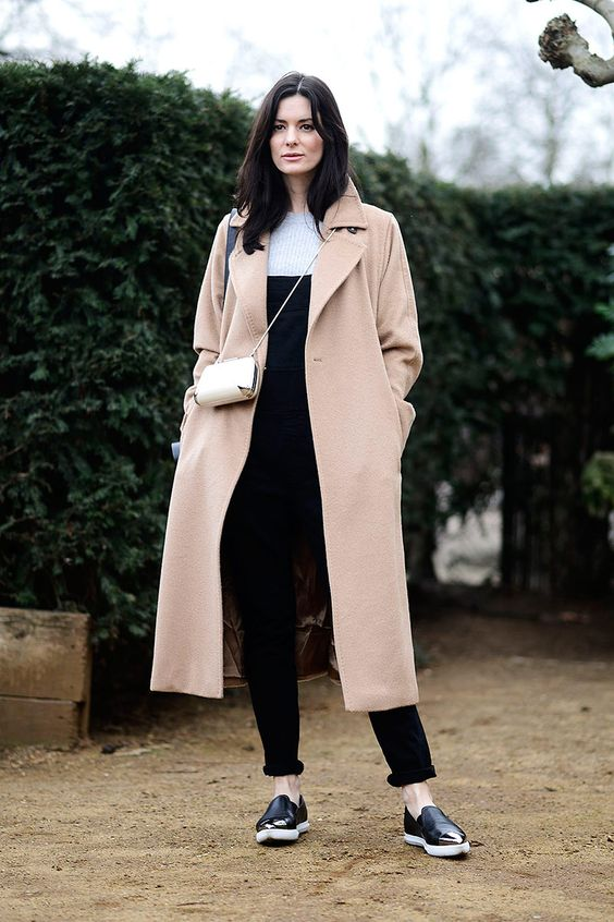 a white top, a black overall, black slipons, a blush midi coat and a creamy mini bag