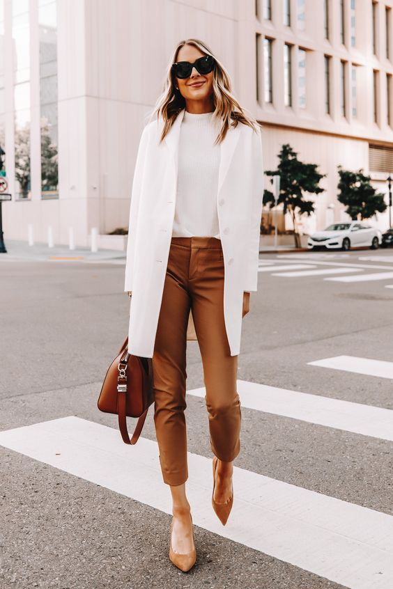 a white top, a white short trench, camel leather pants, camel shoes and a brown bag