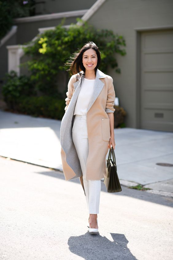 a white top and trousers, white shoes, a two tone trench in grey and tan and a black bag